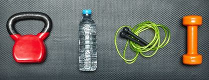 Gym concept. dumbbell, skipping rope,training weight and bottle of water on step equipment background.Healthy lifeslile. Gym concept. dumbbell, skipping rope stock images