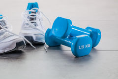 Gym concept with running sneakers and weights for wellness lifestyle Royalty Free Stock Photography