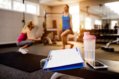 Gym details, women exercising, clipboard, water bottle, smart ph Royalty Free Stock Photography