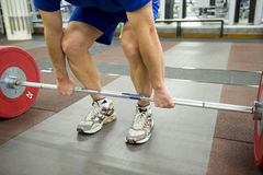 Gym equipment. Gym or gymnasium equipment in a world-class facility suitable for athletes training for international events. Athlete about to lift a set of stock images