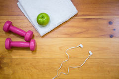 Gym equipment and apple kept on wooden floor Royalty Free Stock Images