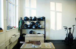 Gym Equipment. Background image of various equipment in gym: medballs on stand, jumping boxes and exercising machines Stock Photography
