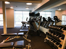 Gym equipment including treadmills and free weights. An exercise area inside a gym containing empty gym equipment including free weights, treadmills, and a royalty free stock photo