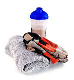 Gym equipment: towel, gloves, postworkout drink. Gym equipment: towel, gloves and shaker with postworkout whey protein shake isolated on white background Royalty Free Stock Photo