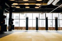 Gym espaçoso com janelas panorâmicos e três sacos de perfuração imagens de stock