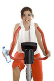 Gym exercise. Young woman training on exercise bike at the gym whit a bottle of water on the left hand Stock Image