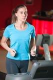 Gym exercising. Run on on a machine. Stock Photos