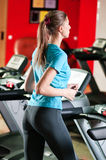 Gym exercising. Run on on a machine. Stock Images