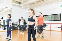Gym fêmea e masculino de Lifts Barbells In do atleta imagens de stock