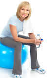 Gym & Fitness. Smiling elderly woman working out. Isolated over white background royalty free stock image