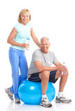 Gym & Fitness. Smiling elderly couple working out. Isolated over white background royalty free stock photo