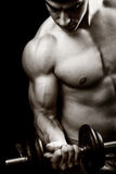 Gym and fitness concept - bodybuilder and dumbbell. Over black Royalty Free Stock Image