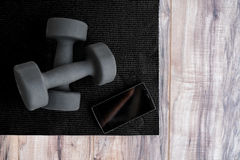 Gym fitness mat with free weights mobile phone app Royalty Free Stock Images