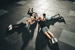 Gym friends planking together during a workout class. High angle of a fit group of diversre people in sportswear planking together on the floor of a gym during royalty free stock images