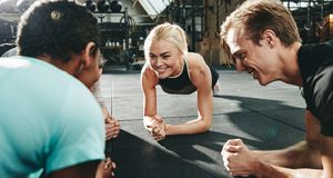 Gym friends smiling and planking together during a workout class. Smiling group of diverse people in sportswear planking together on the floor of a gym during an stock photography