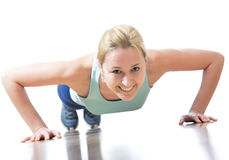 Gym girl. Young beautiful sportswoman exercising (doing push-up Royalty Free Stock Image