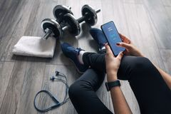 The girl opened the fitness application on the smartphone. In the gym the girl is using a smartphone royalty free stock image