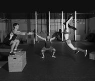 Gym group workout barbells slam balls and jump. Gym people group workout barbells slam balls and jump exercises royalty free stock images