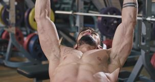 A gym guy is doing heavy lifts while flexing his muscles, and getting them perfect abs.  stock footage