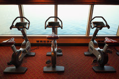 Gym hall with exercise bicycle near window Stock Photography