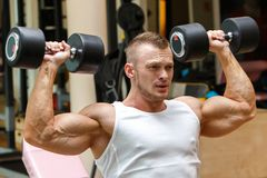 Gym. Handsome man during workout Stock Photo