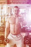 Gym. Handsome man during workout Royalty Free Stock Photo