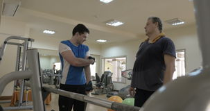 Gym instructor giving consultation to a man stock footage
