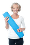 Gym instructor holding blue exercise mat Royalty Free Stock Images