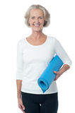 Gym instructor holding blue exercise mat Stock Images