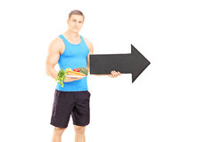 Gym instructor holding dish and big black arrow pointing right Royalty Free Stock Photo