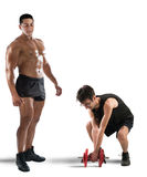 Gym instructor mockingly. Instructor teases an awkward and skinny boy Stock Photo