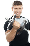 Gym instructor posing with heavy dumbbell Royalty Free Stock Images