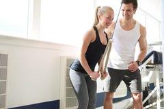 Gym instruktor Pomaga kobiety na Pulley przyrządzie zdjęcie stock