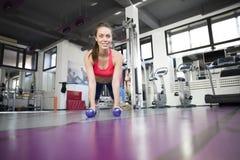 Gym kobieta robi pushup ćwiczeniu z dumbbell w gym Obrazy Royalty Free