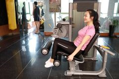 Gym leg extension exercise workout woman indoor. Beautiful, press. Gym seated leg curl machine exercise woman at indoor stock photos