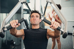 Gym: Man Concentrates While Doing Arm Workout Royalty Free Stock Images