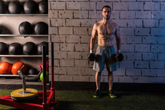 Gym man holding hex dumbbells with muscles Stock Photography