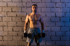 Gym man holding hex dumbbells with muscles Stock Photos