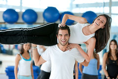 Gym man lifting a woman Royalty Free Stock Photo