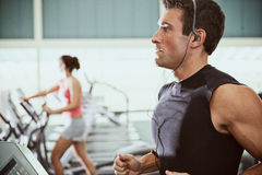 Gym: Man Listens to Music While Jogging On Treadmill Royalty Free Stock Photo