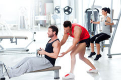 Gym man with personal trainer and fitness woman Royalty Free Stock Photos