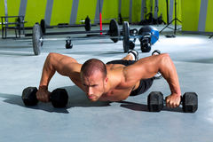 Gym man push-up strength pushup exercise with dumbbell Stock Photos