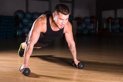 Gym man push-up strength pushup exercise with dumbbell in a fitness workout.  stock images