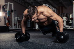 Gym man push-up strength pushup exercise with dumbbell Royalty Free Stock Images