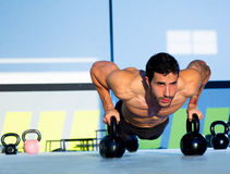 Gym man push-up strength pushup with Kettlebell. Gym man push-up strength pushup exercise with Kettlebell in a crossfit workout royalty free stock image