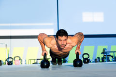 Gym man push-up strength pushup with Kettlebell Stock Photo