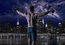 Gym man rising hex dumbbells in New York city. Skyline at night rear view photo mount stock images