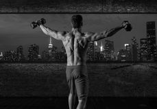 Gym man rising hex dumbbells in New York city. Skyline at night rear view photo mount stock image