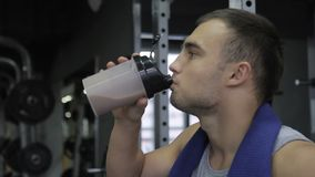 In the gym man with a towel around his neck drinks a protein cocktail. stock video footage