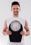 Gym man with a weight scale Royalty Free Stock Photography